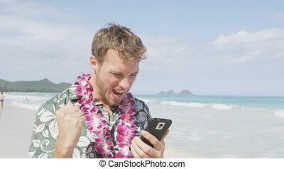 Celebrating man winning on smart phone app beach - ...