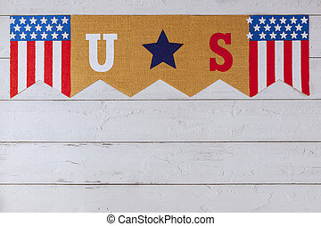 Celebrating US. federal holiday with US word of letters in the America flag on wood background