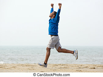 Celebrating victory - Happy young man running outdoors and ...