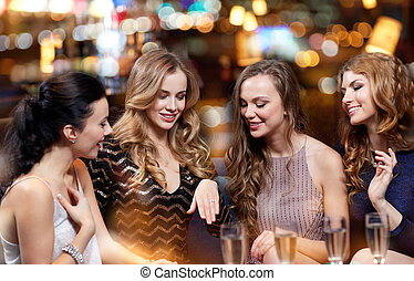 woman showing engagement ring to her friends - celebration,...