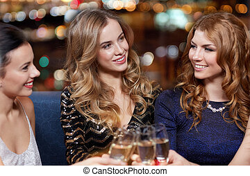 happy women with champagne glasses at night club -...