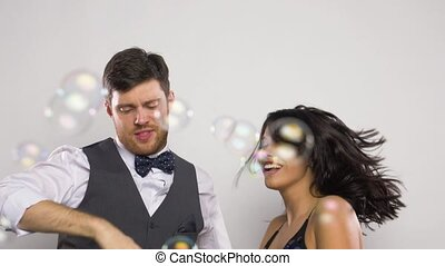 happy couple dancing in soap bubbles at party - celebration,...