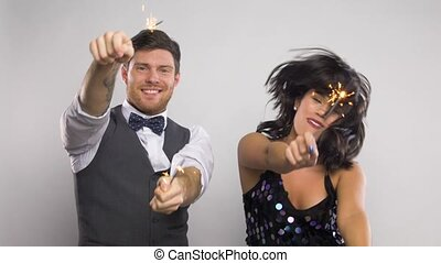 happy couple with sparklers dancing at party
