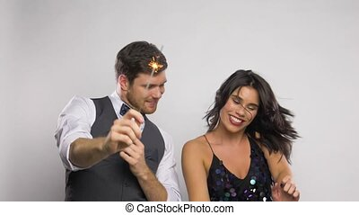 happy couple with sparklers dancing at party - celebration,...