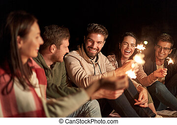 happy friends with sparklers at night outdoors