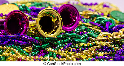 Celebration horns on a background of colorful Mardi Gras beads