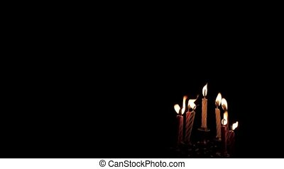 Burning candles for the Jewish holiday of Hanukkah on a black isolated background in 4K without people.