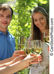 Celebration. People holding glasses of white wine making a...