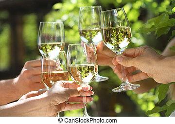 Celebration. People holding glasses of white wine making a toast. Shallow DOF.