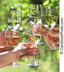 People holding glasses of white wine making a toast -...