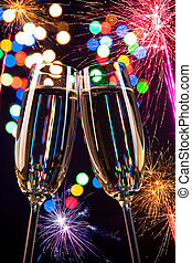 Celebration theme - Champagne glasses with fireworks on...