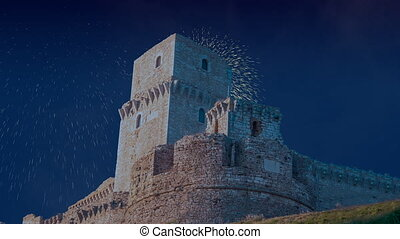 Celebratory fireworks for new year over rocca maggiore in assisi, a medival tower up a hill during last night of year. Christmas atmosphere