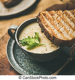 Celery cream soup and toast over linen tablecloth, square crop