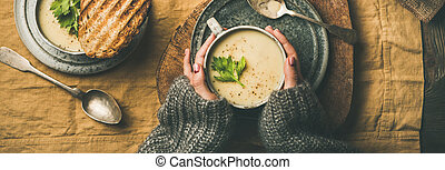Celery cream soup, grilled bread and female hands, wide composition