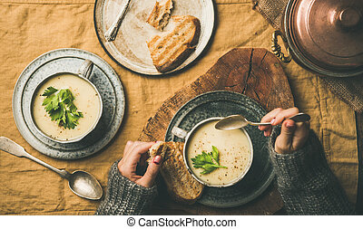 Celery cream soup in cups and female hands with spoon