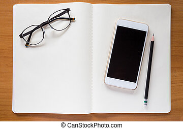 Cell phone, eyeglasses, and pencil on white notebook
