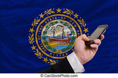 cell phone in front flag of american state of new hampshire