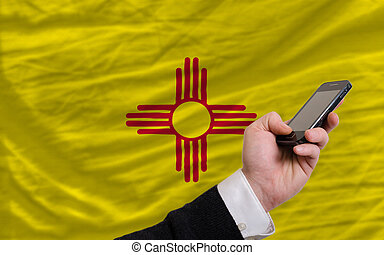 cell phone in front flag of american state of new mexico