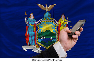 cell phone in front flag of american state of new york