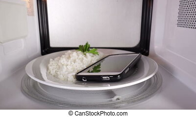 Cell phone with rice on a plate heating in the microwave oven