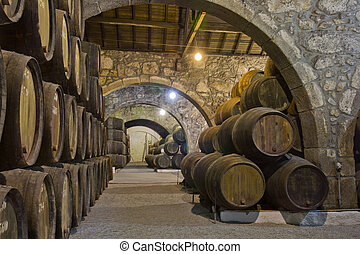 old cellar with rows of wooden wine barrels
