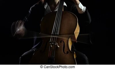 Cellist playing a musical composition .Black background