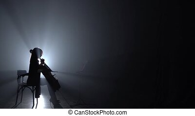 Cellist playing her instrument in a dark room and looking notes. Silhouette. Black smoke background. Side view