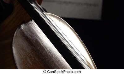 Cello close up of bows carry on the string with notes in a dark room. Side view. Slow motion