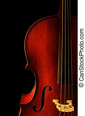 Cello, in close-up with black background. Natural warm light...