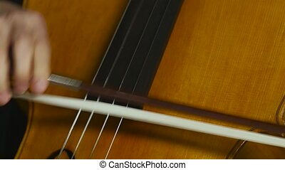 Cello musical instrument close up bowing on strings. Clos...