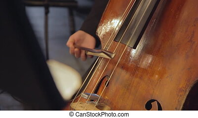 Cello player. Cellist hands playing cello with bow closeup. classic music concept.