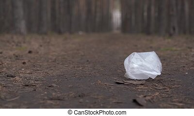 Cellophane bag on ground in forest. Concept of environmental pollution