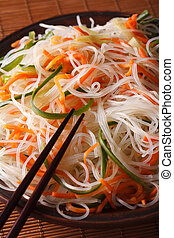 Cellophane noodle salad with cucumber and carrot on a plate close-up. vertical