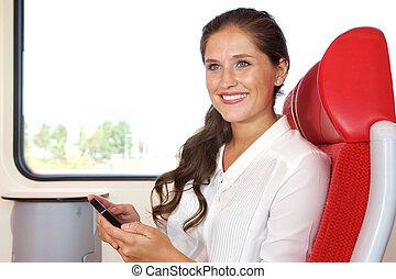 cellphone, kobieta handlowa, pociąg, używając, szczęśliwy