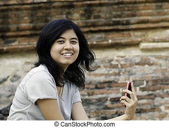 cellphone, mulher, enquanto, posar, asiático, segurando
