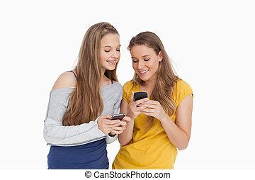 cellphones, medan, deras, se, le, kvinnor, två, ung