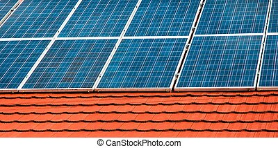 Cells of solar energy panels on the roof of a building