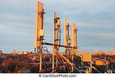 Cellular antennas in the sunset light. Seen in USA.