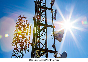 An abstract view of two cellular base station towers, steel lattice design with electronic communications gear on a sunny day with colorful lens flare