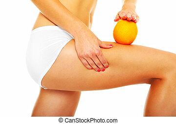 Cellulite treatment - A picture of female legs and an orange...