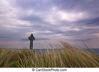 Celtic cross in the island of Inisheer on a dramatic sky
