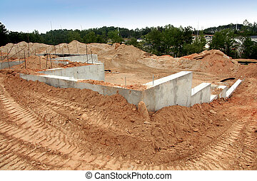 Cement foundation of a brand new home site. There are bulldozer tracks going around it.