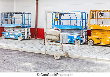 Cement mixer is placed next to a row of cherry pickers