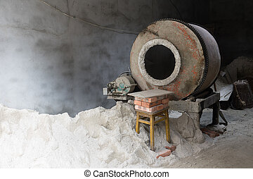 Cement mixer machine at construction site, tools and sand