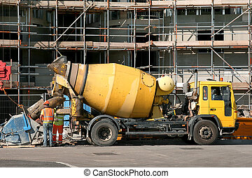 Cement Mixer Truck - Yellow cement mixer truck in front of a...