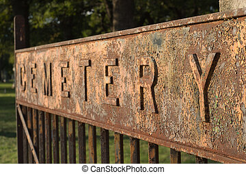 Cemetary spelled out in large letters on a sign on the entrance gate to a cemetary. Focus is on the nearest letter Y.