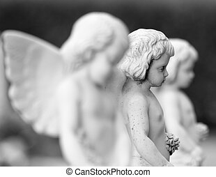 cemetery angel statues with flowers in hands, Italy -...