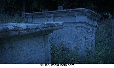 Couple of old stone crypts in cemetery at dusk