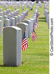 United States American Flags decorate the gravestones of veterans at a USA national cemetery on Memorial Day.