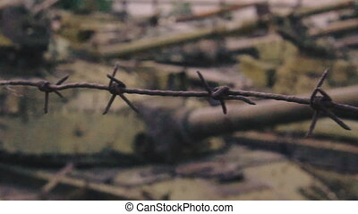 Cemetery military equipment. Under the barbed wire warehouse rusty tanks